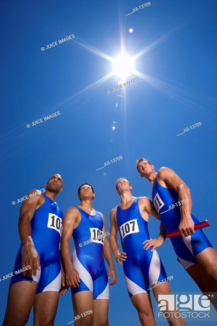 Stock Photo: Group of male athletes, low angle view, lens flare.