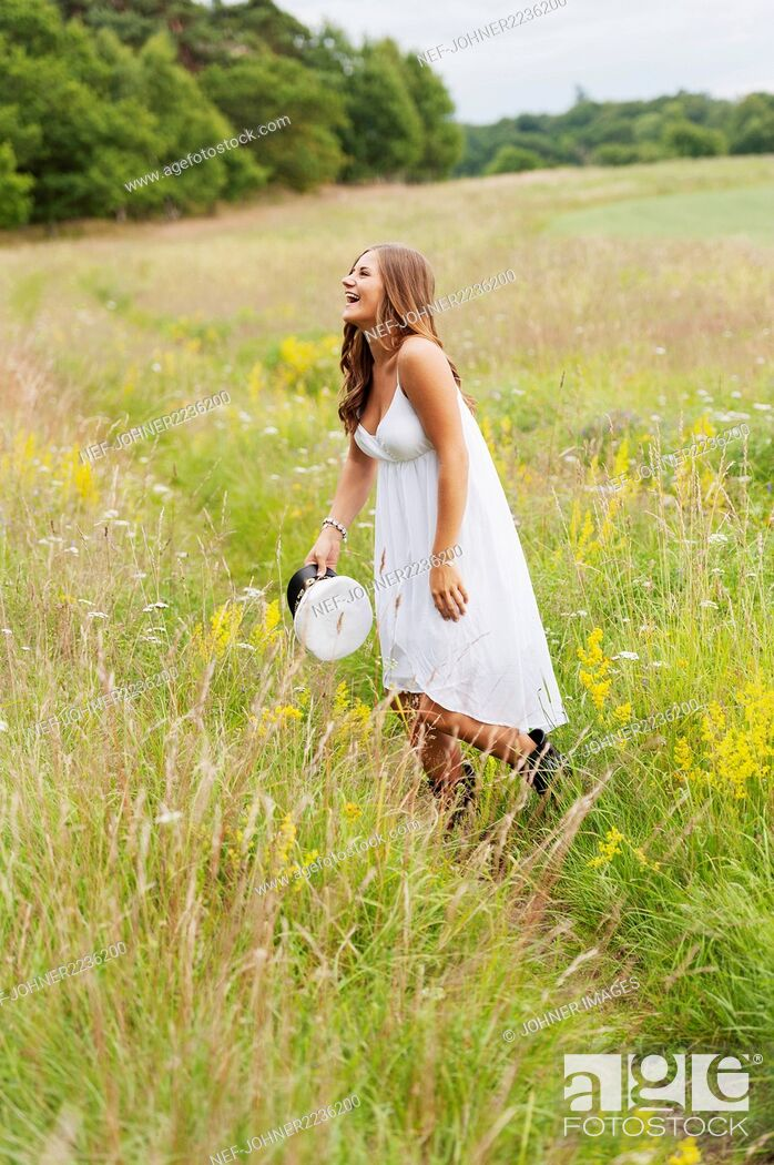Stock Photo: Young woman throwing hat in field.