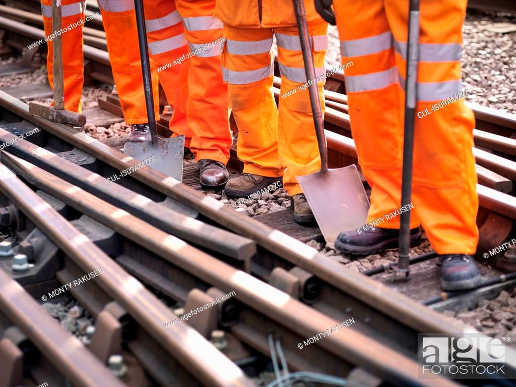 Imagen: Railway maintenance workers standing with tools on track, low section.