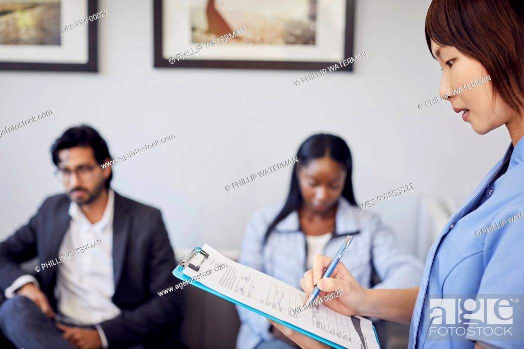 Stock Photo: Receptionist checking form in waiting room of a dental practice.