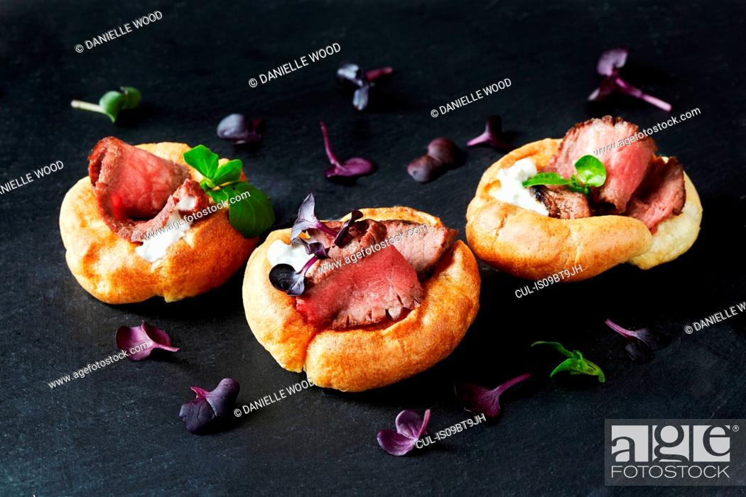 Stock Photo: Still life with canapes of roast beef in yorkshire puddings on black slate.