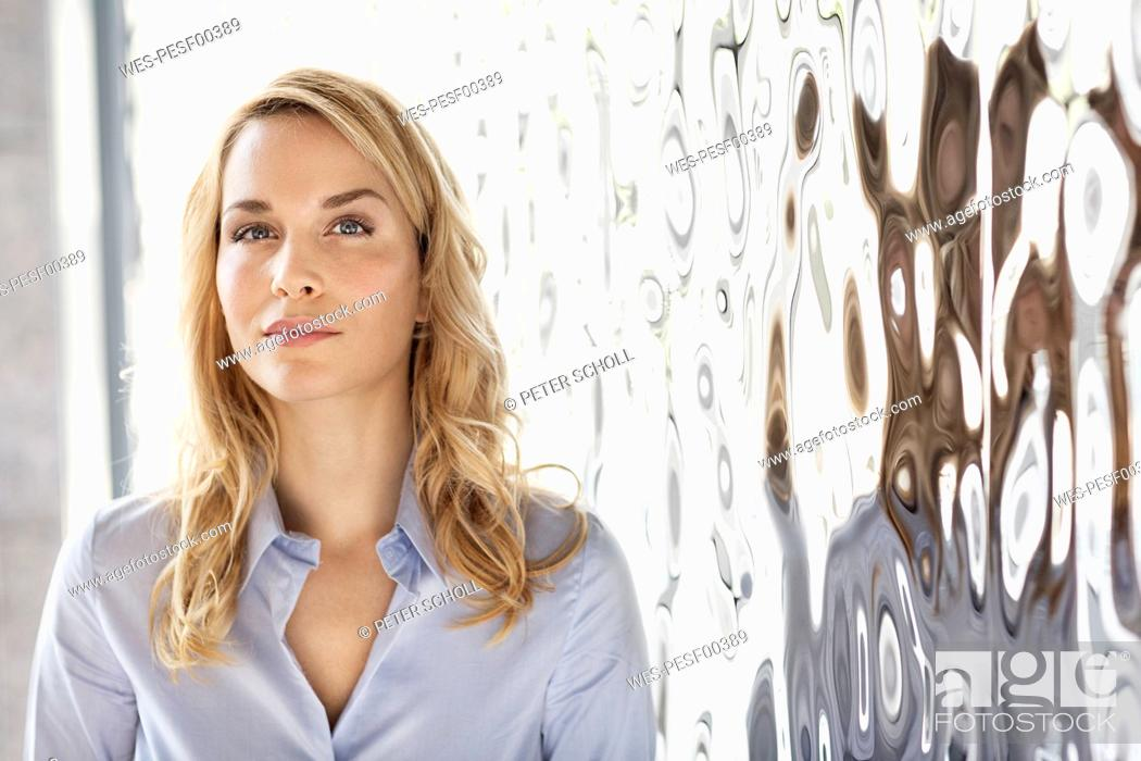 Stock Photo: Portrait of confident businesswoman at rippled wall.