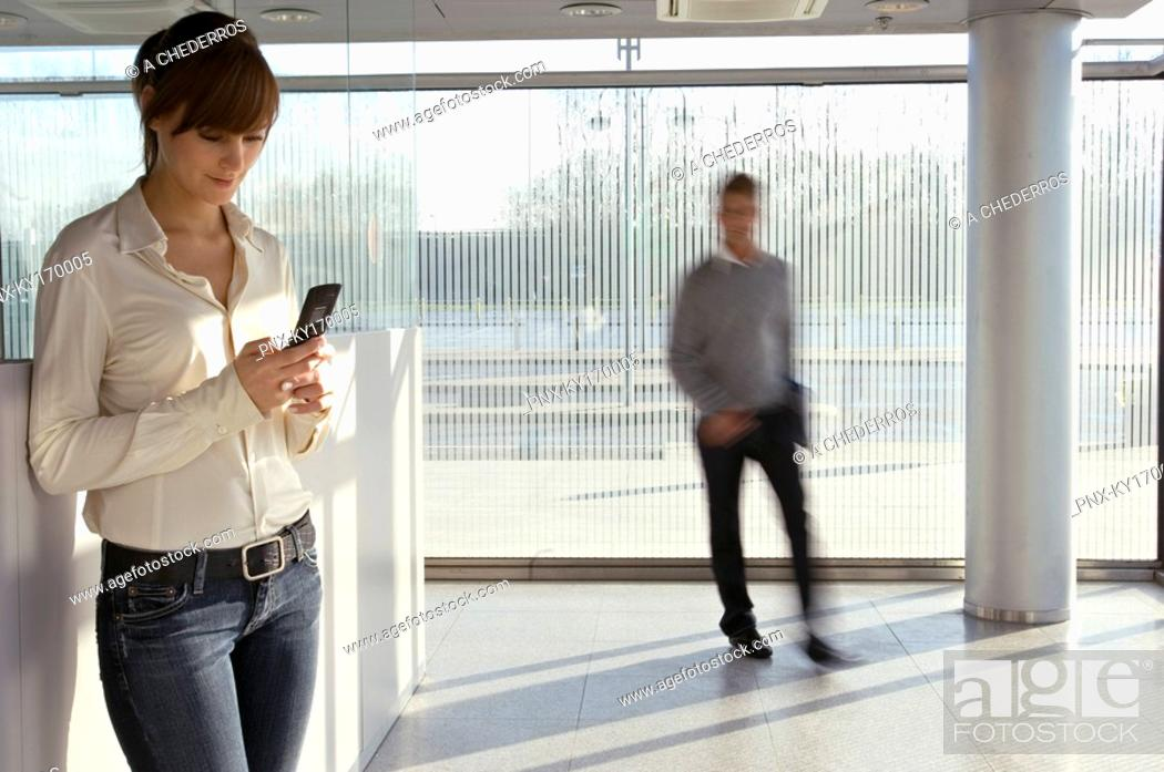 Stock Photo: Businesswoman using a mobile phone with a businessman walking in the background.