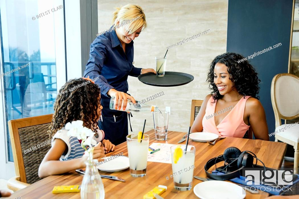 Stock Photo: Server pouring water for mother and daughter at restaurant.