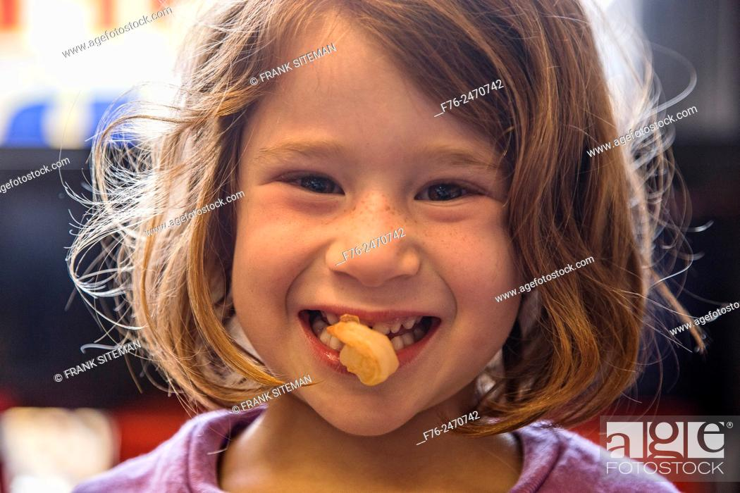 Stock Photo: 6 year old girl with a cooked shrimp in her mouth in a noodle restaurant in Berkeley, CA, USA.