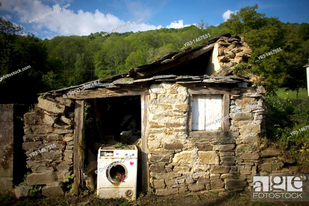 Stock Photo: A broken washing machine blocks the door of an abandoned house located in the French Way that leads to Santiago de Compostela, Spain.