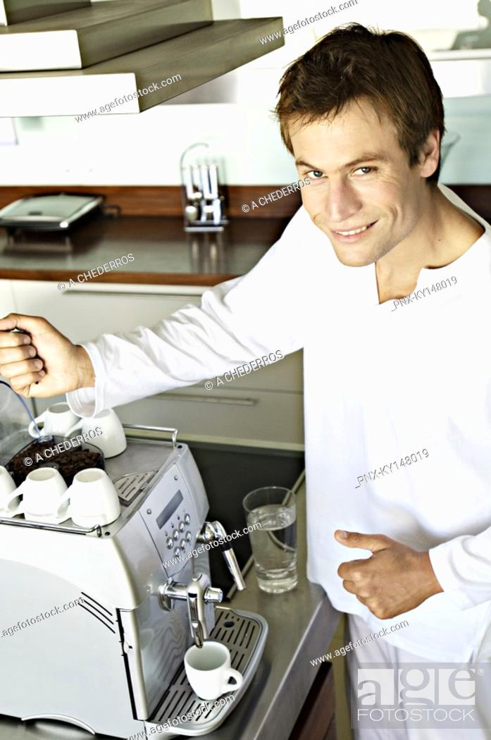 Stock Photo: Young smiling man in front of espresso maker.