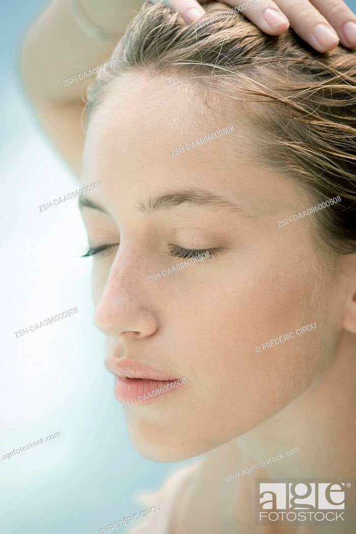 Stock Photo: Young woman with hand on head, eyes closed, portrait.