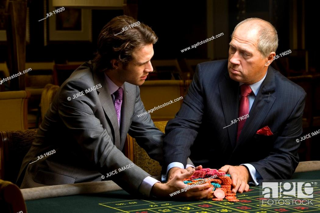 Stock Photo: Mature man giving young man pile of gambling chips at roulette table.