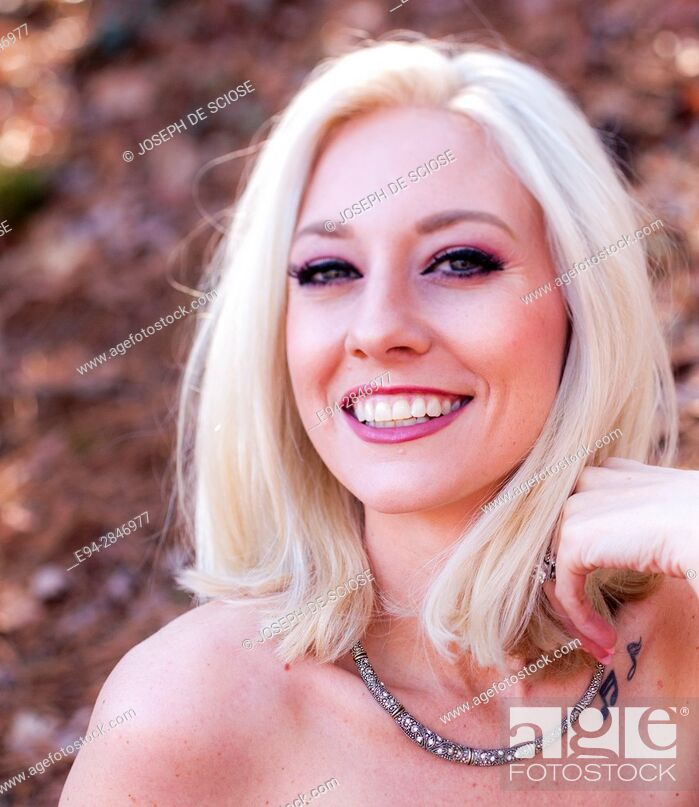 Stock Photo: Portrait of a 30 year old blond woman smiling at the camera, outdoors.
