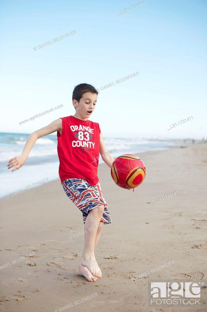 Stock Photo: Boy playing football at the beach, El Saler beach, Albufera de Valencia Nature Reserve, Spain, Valencia.