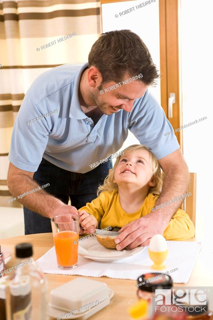 Stock Photo: Father spreading butter on bread for daughter breakfast.