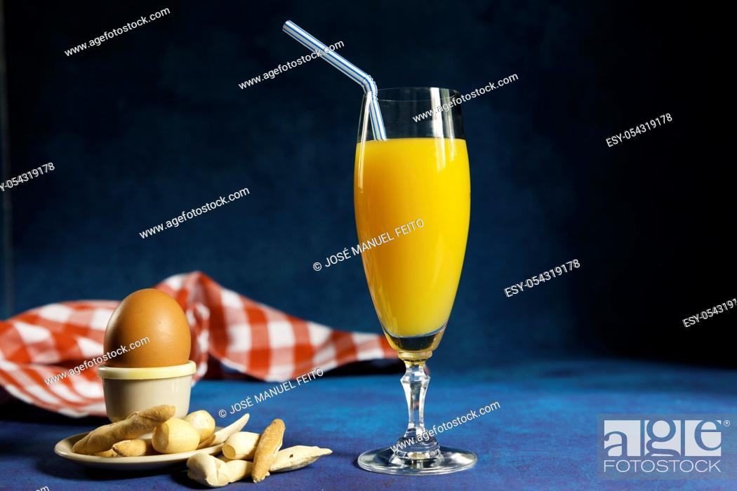 Stock Photo: glass of orange juice with a straw, boiled egg in an egg cup with bread and napkin on blue fantasy background.