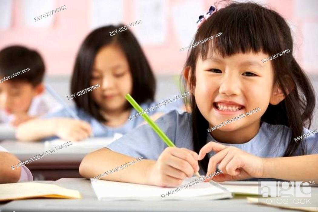 Stock Photo: Group Of Students Working At Desks In Chinese School Classroom.