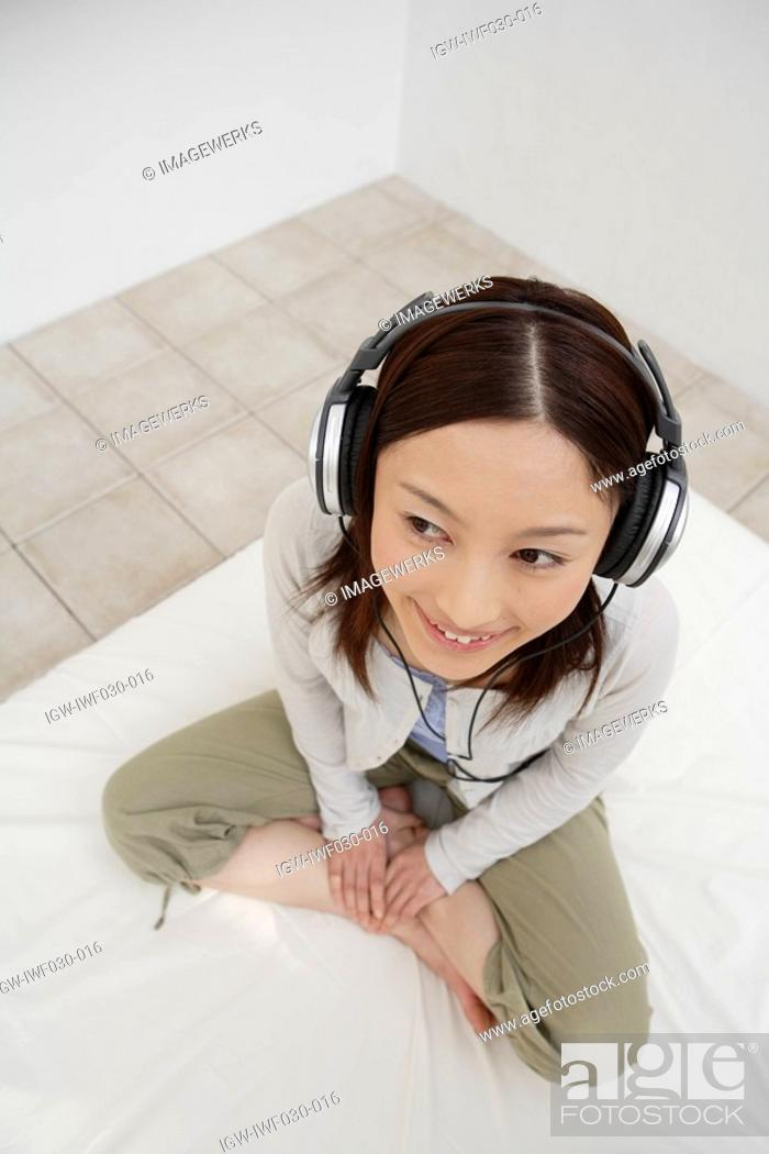 Stock Photo: View of a young woman using a headphone.