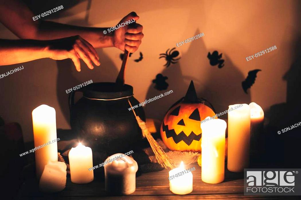 Stock Photo: witch hand boiling potion for spell, with jack o lantern pumpkin with candles, broom and bats, ghosts on background in dark spooky room.