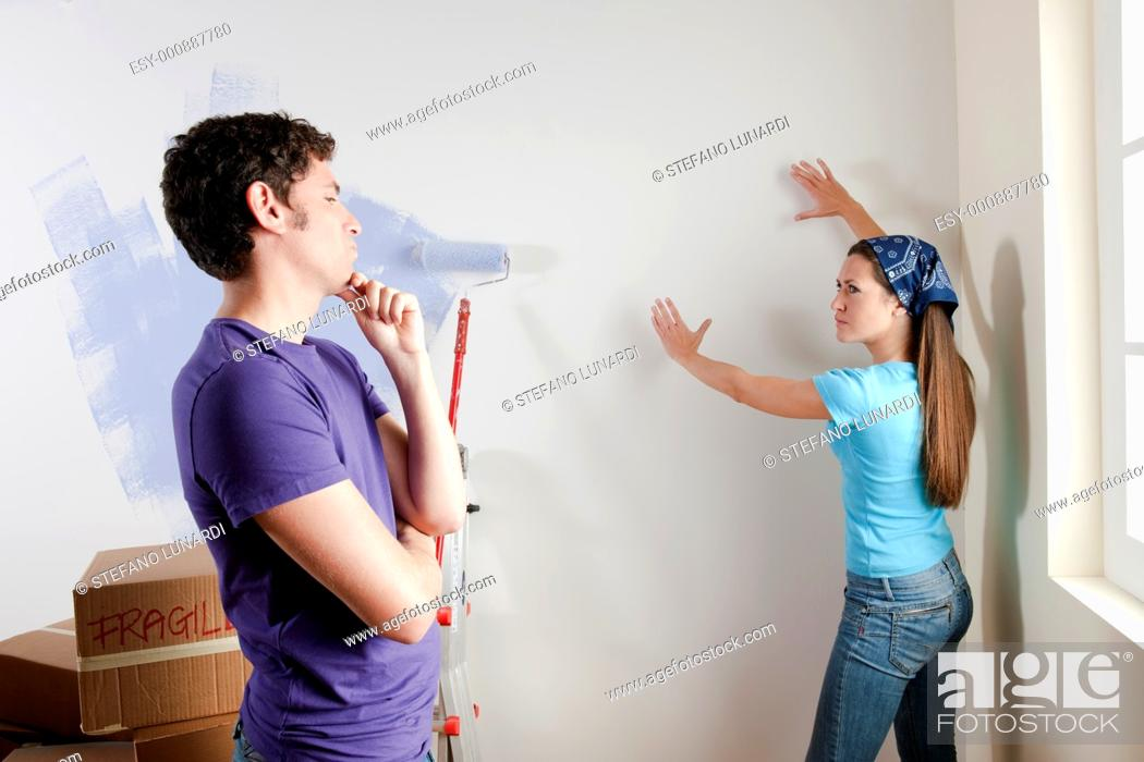 Stock Photo: Young couple discussing about where to place paintings or pictures.