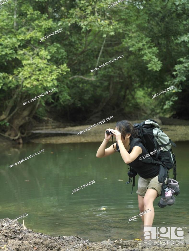 Stock Photo: Young woman standing in water carrying backpack looking through binoculars.