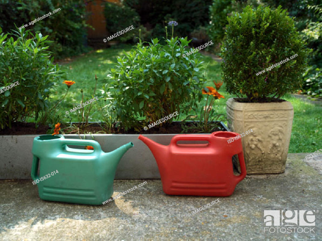 Stock Photo: A pair of watering cans in garden.