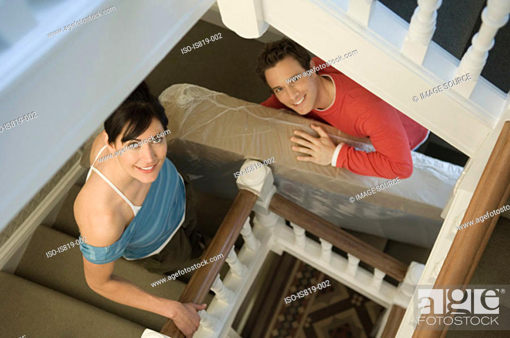 Stock Photo: Couple carrying mattress up stairs.