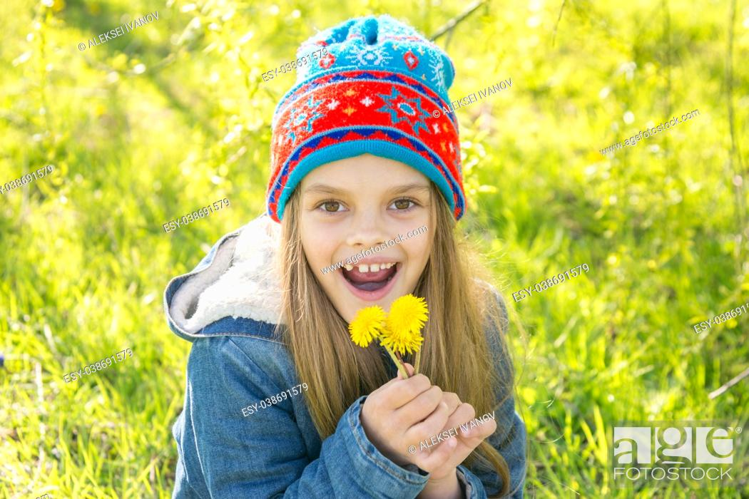 Photo de stock: Seven-year-old girl in the spring is pleased with the blossoming dandelions.