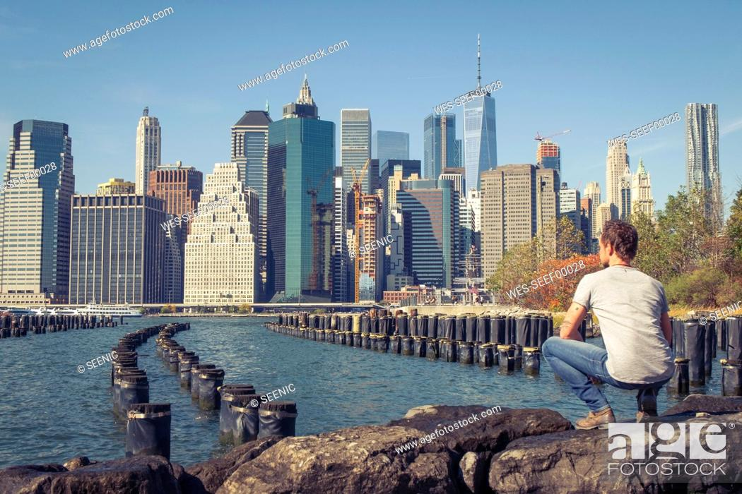 Imagen: USA, New York City, man looking at skyline with One World Trade Center.