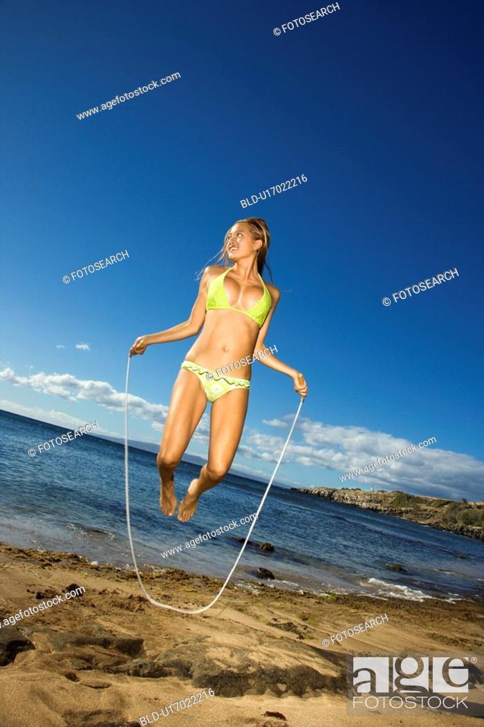 Stock Photo: Young adult Asian Filipino female in bikini jumping rope on beach.