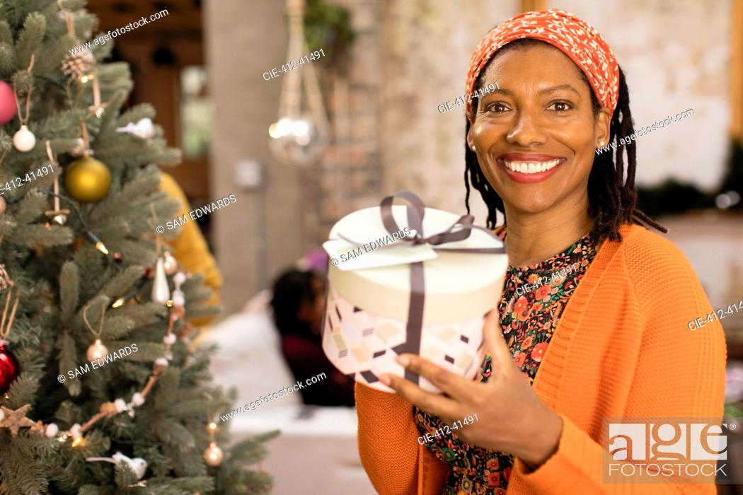 Stock Photo: Portrait smiling, confident woman holding gift next to Christmas tree.