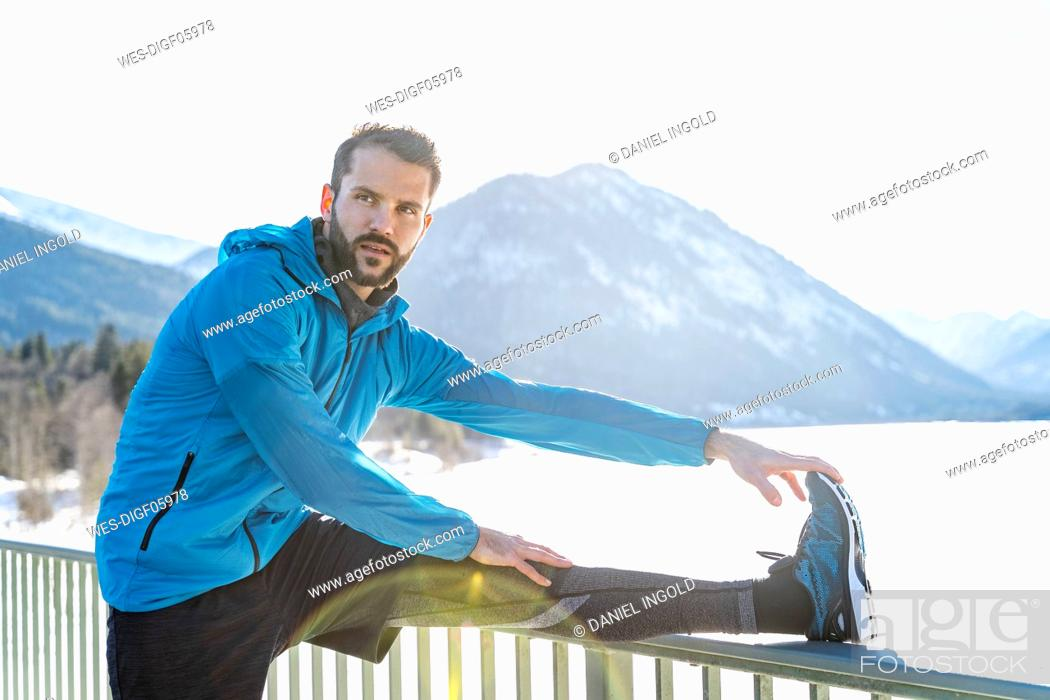 Photo de stock: Germany, Bavaria, sportive man stretching in winter on bridge railing.