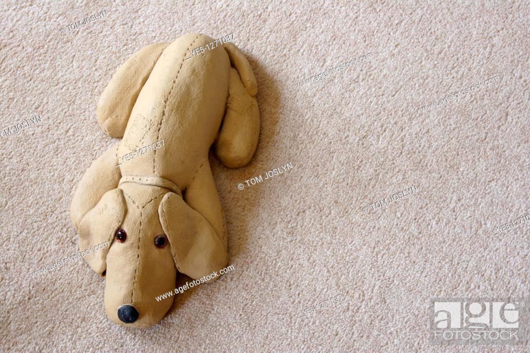 Stock Photo: Ornamental dog lying on carpet.