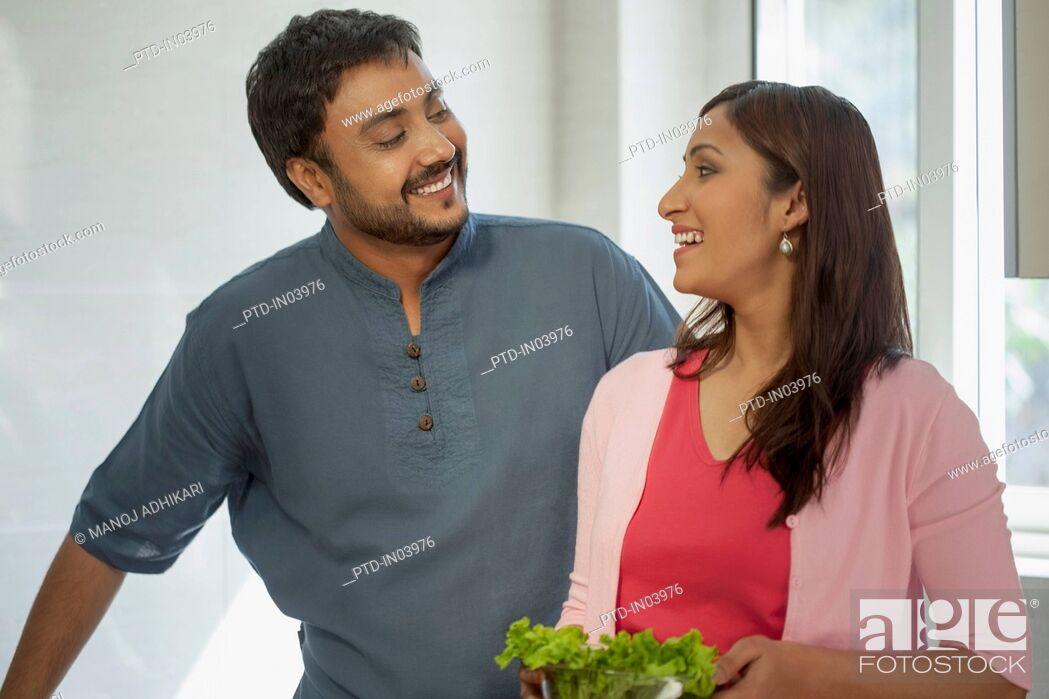 Stock Photo: India, Man and woman standing in kitchen holding salad bowl.