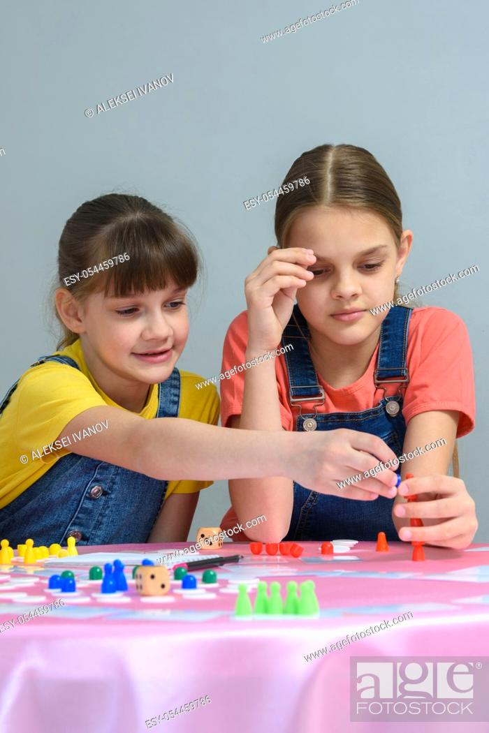 Stock Photo: Two girls enthusiastically play a board game.