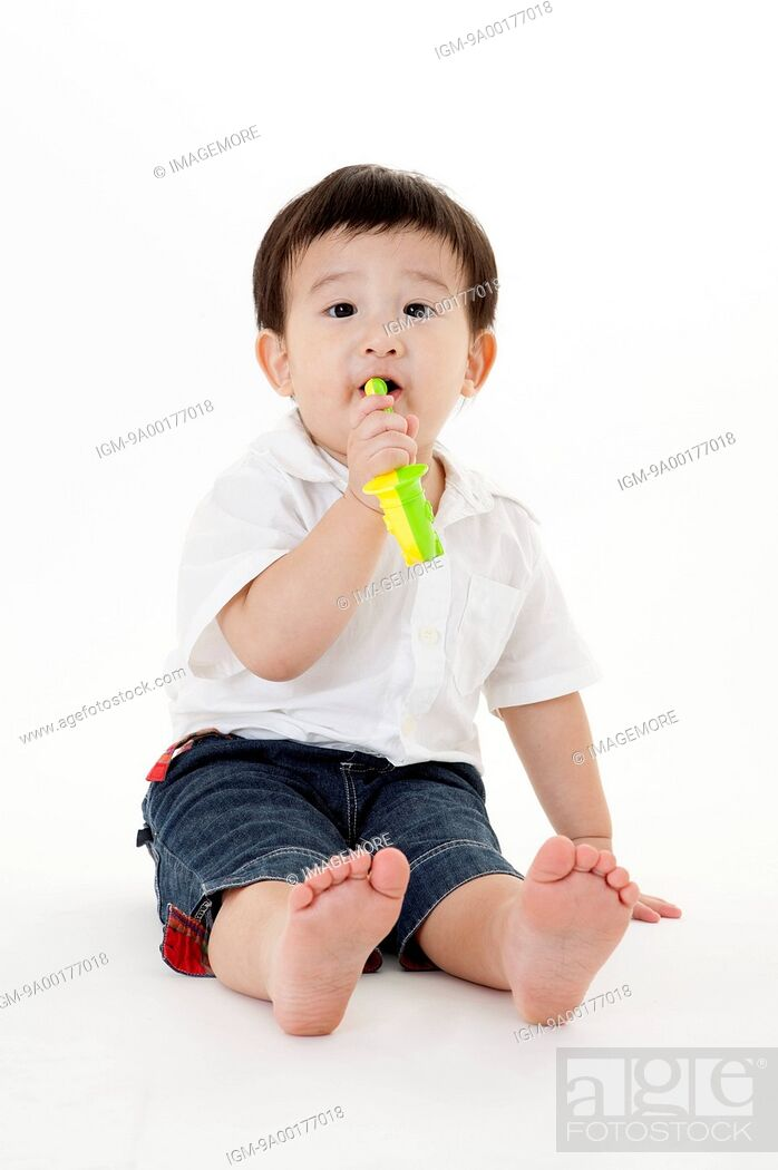 Imagen: Baby boy sitting on the ground and playing toy.