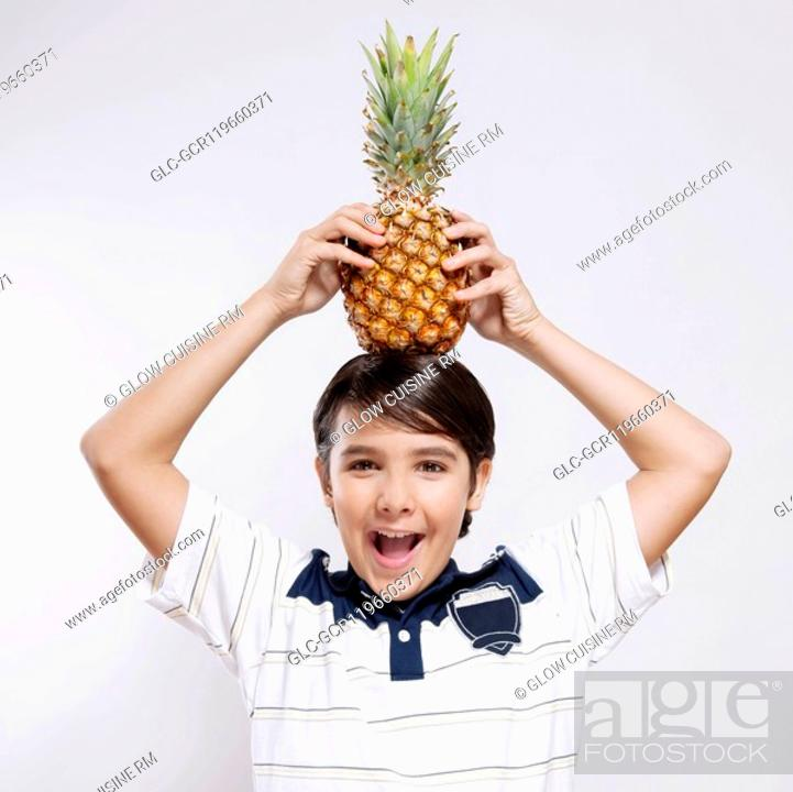 Stock Photo: Portrait of a boy carrying a pineapple on his head.