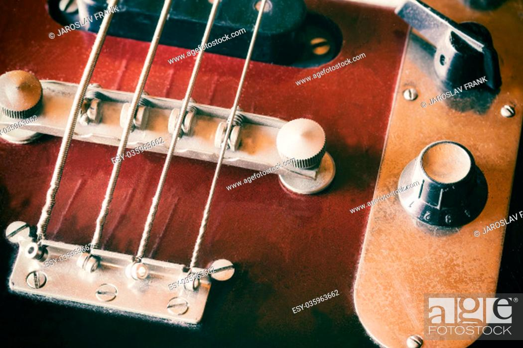 Stock Photo: Used electric bass guitar closeup. Edited as a vintage photo with dark edges. All potential trademarks are removed.