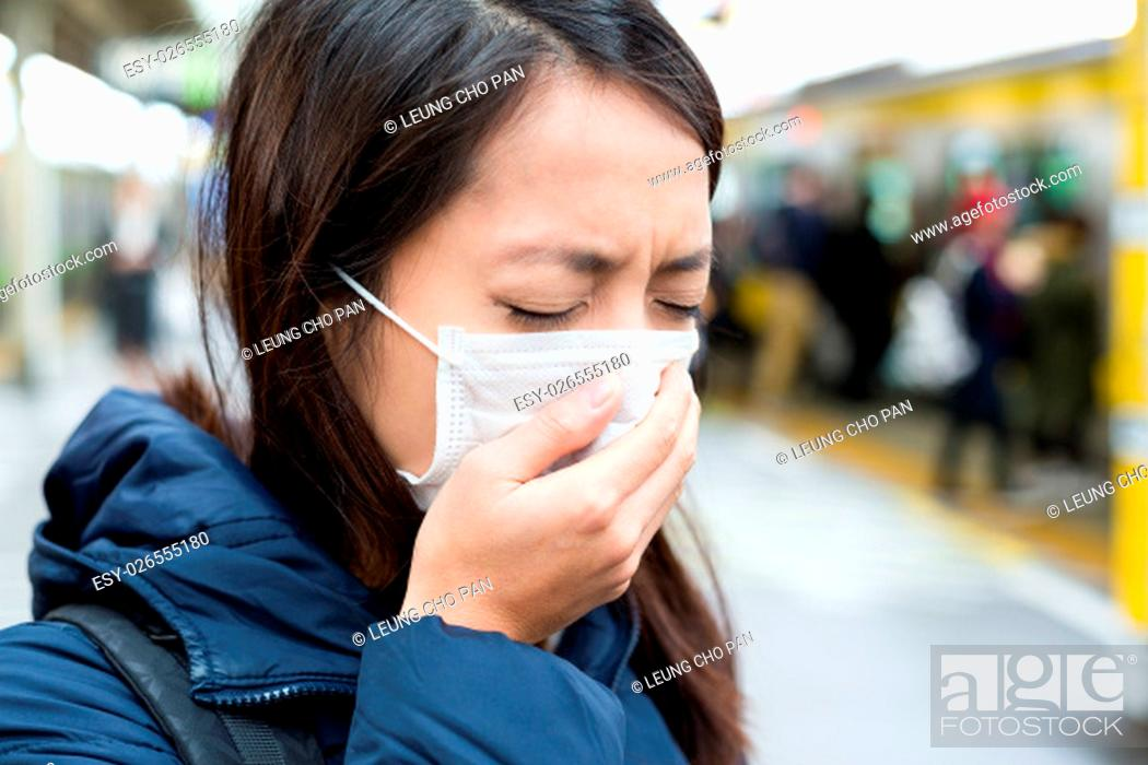 Stock Photo: Asian woman wearing face mask at train station.