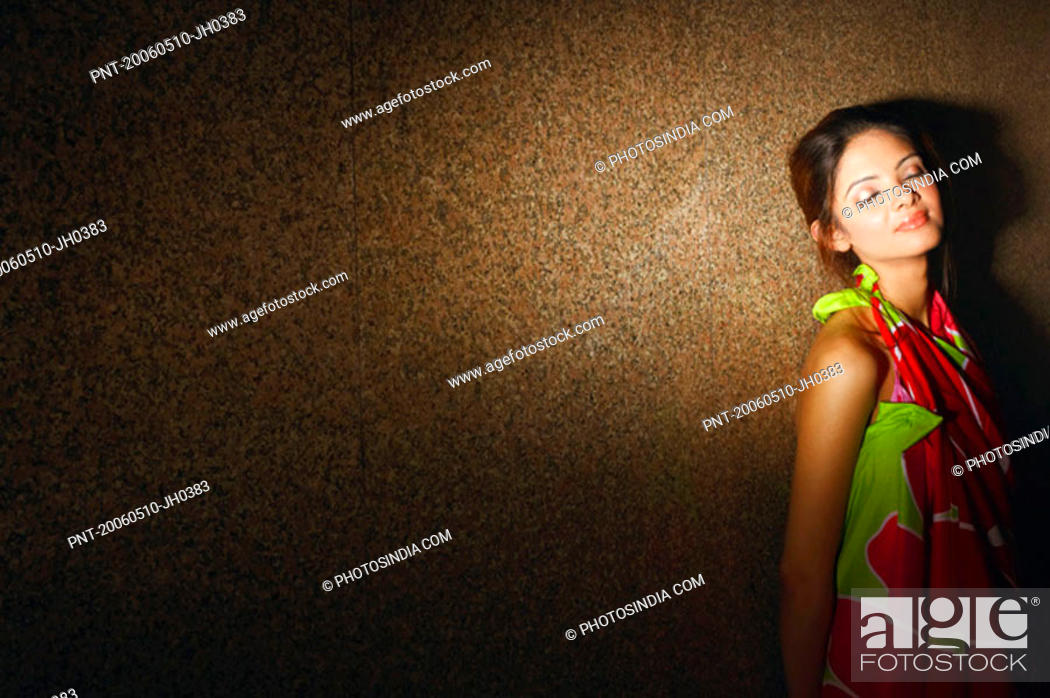 Stock Photo: Young woman leaning against a wall and smiling.