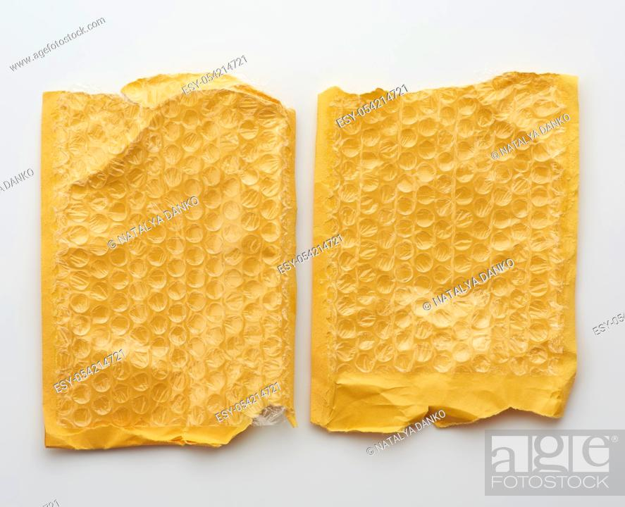 Stock Photo: fragment of a transparent film with air for transportation of parcels is glued on a yellow sheet of paper, inside of the envelope on a white background.