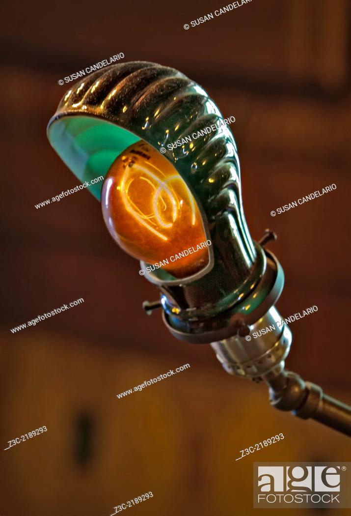 Stock Photo: Thomas Edison carbon filament light bulb replica in a bankers desk style lamp.