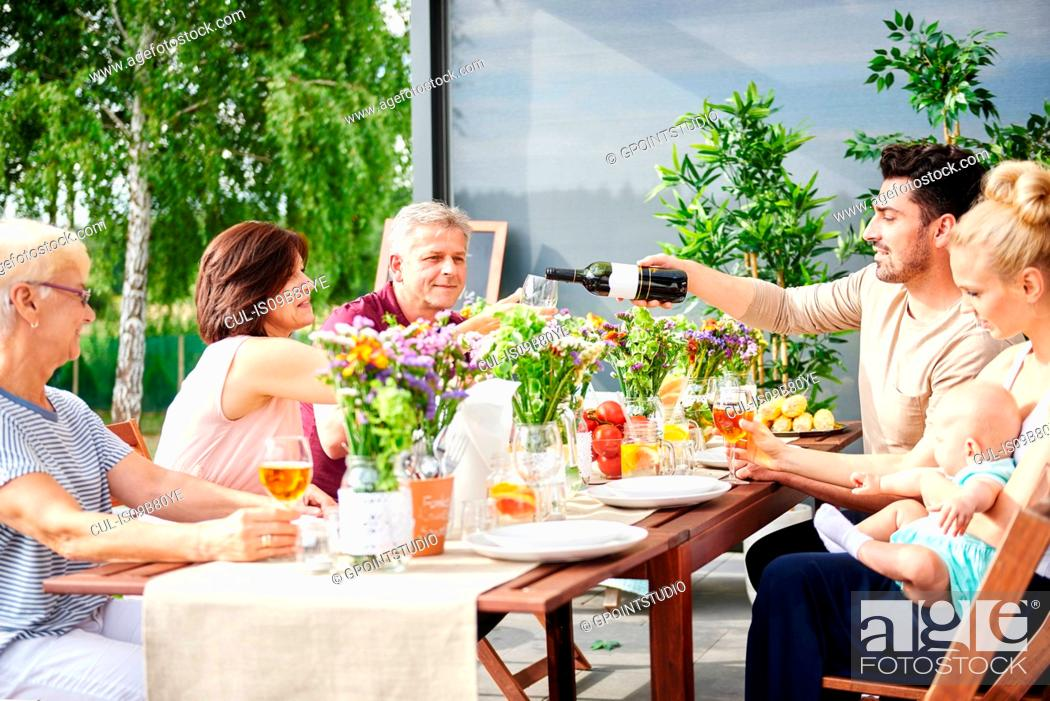 Imagen: Three generation family having lunch and pouring wine on patio table.