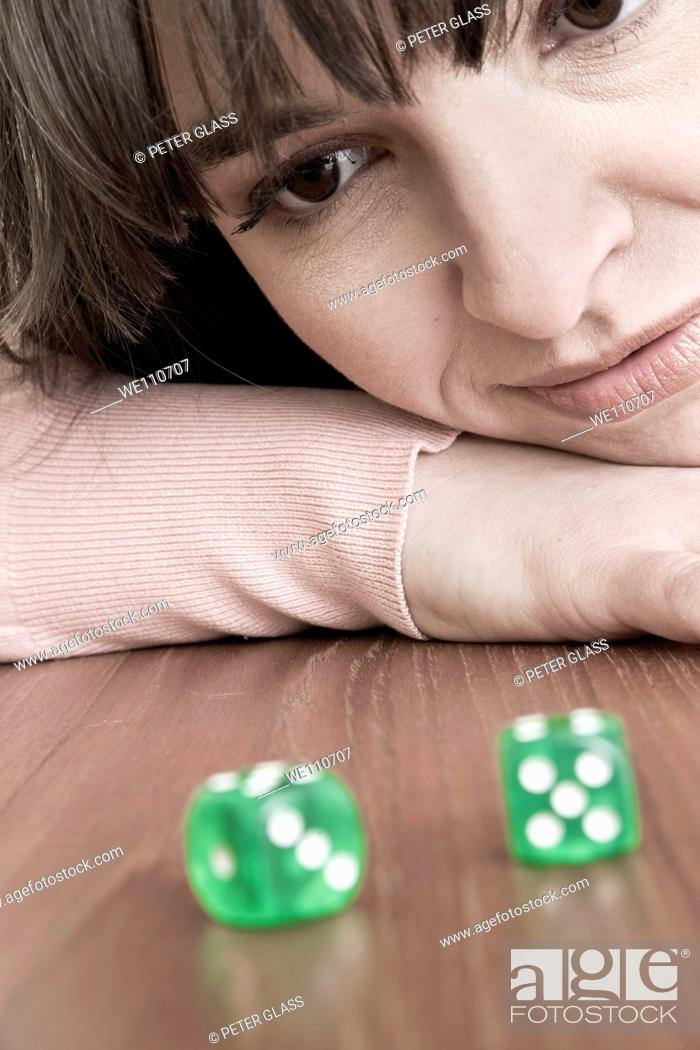 Stock Photo: Young woman looking at a pair of green dice.
