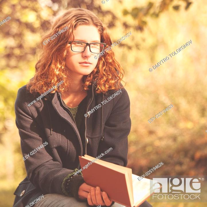 Stock Photo: Young red head woman reading his book in autumnal park.