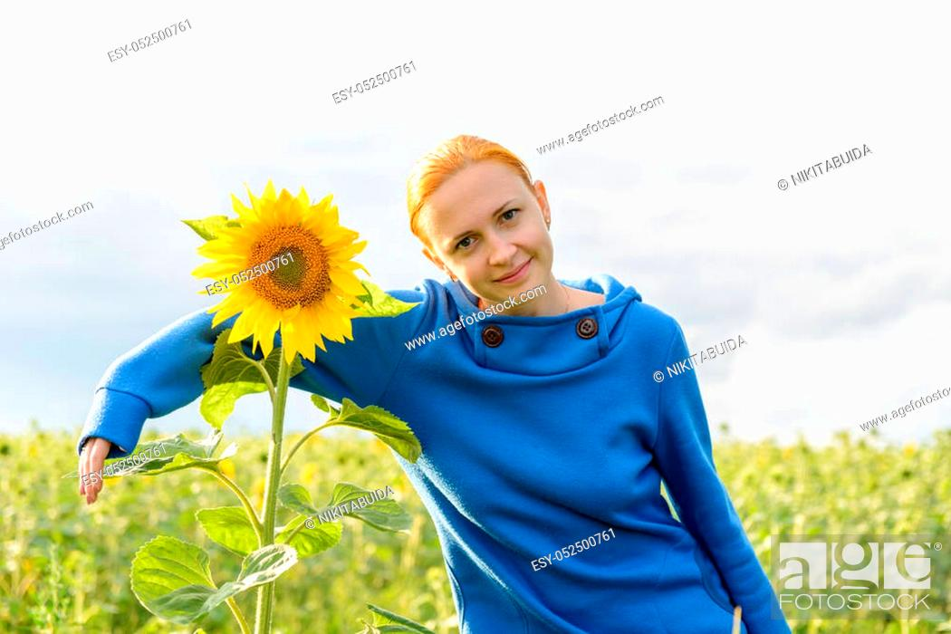 Stock Photo: Young red woman hugs sunflower in the field.