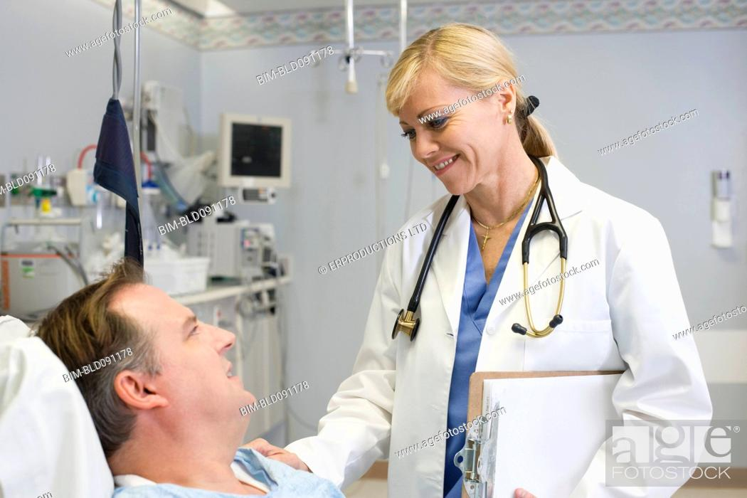 Stock Photo: Doctor comforting patient in hospital bed.