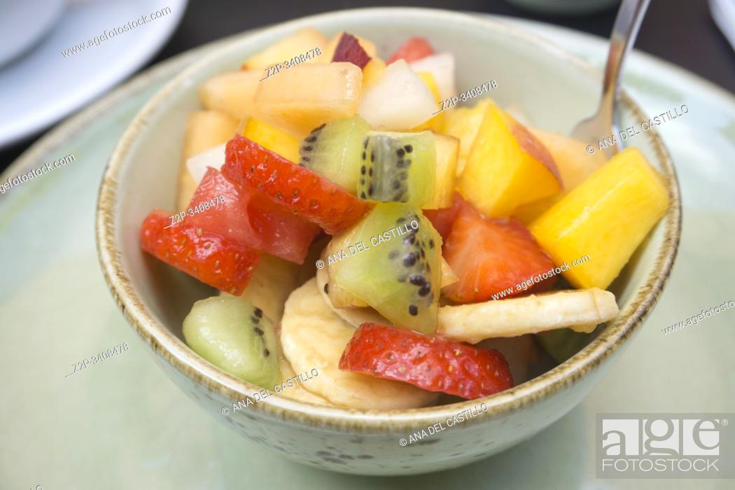 Stock Photo: Sliced summer fruits on a green bowl.