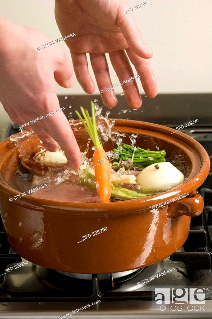 Stock Photo: Adding vegetables to meat in pot-au-feu pot.