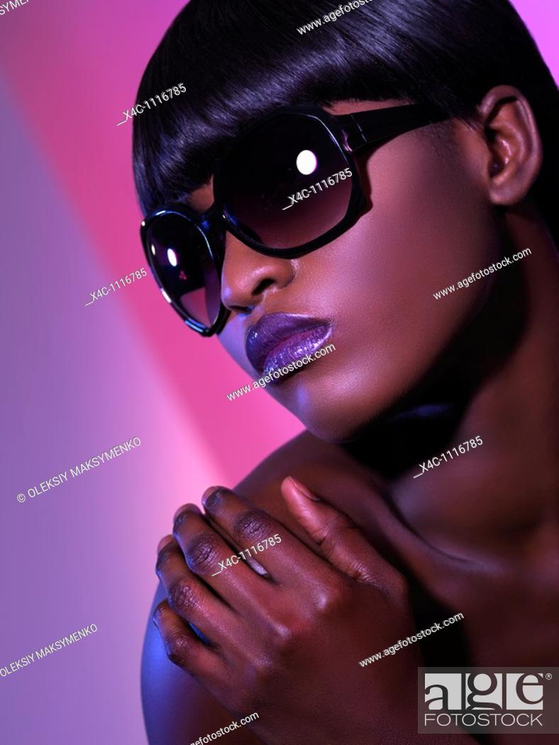 Stock Photo: Beautiful young woman in black sunglasses on purple background  Beauty headshot.