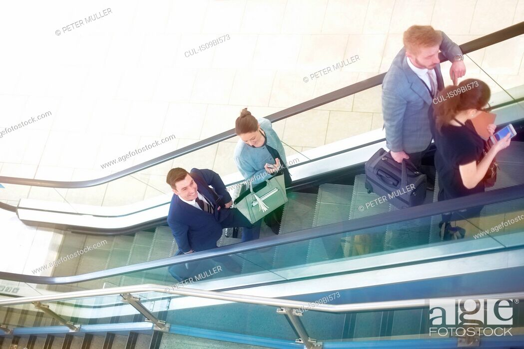 Imagen: Businessmen and women moving up airport escalator, high angle view.
