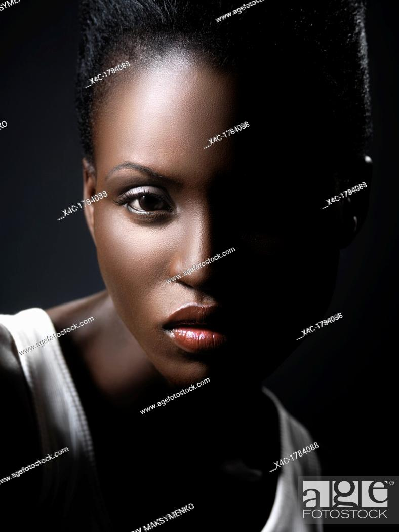 Stock Photo: Young black african woman artistic closeup face beauty portrait with dramatic lighting.