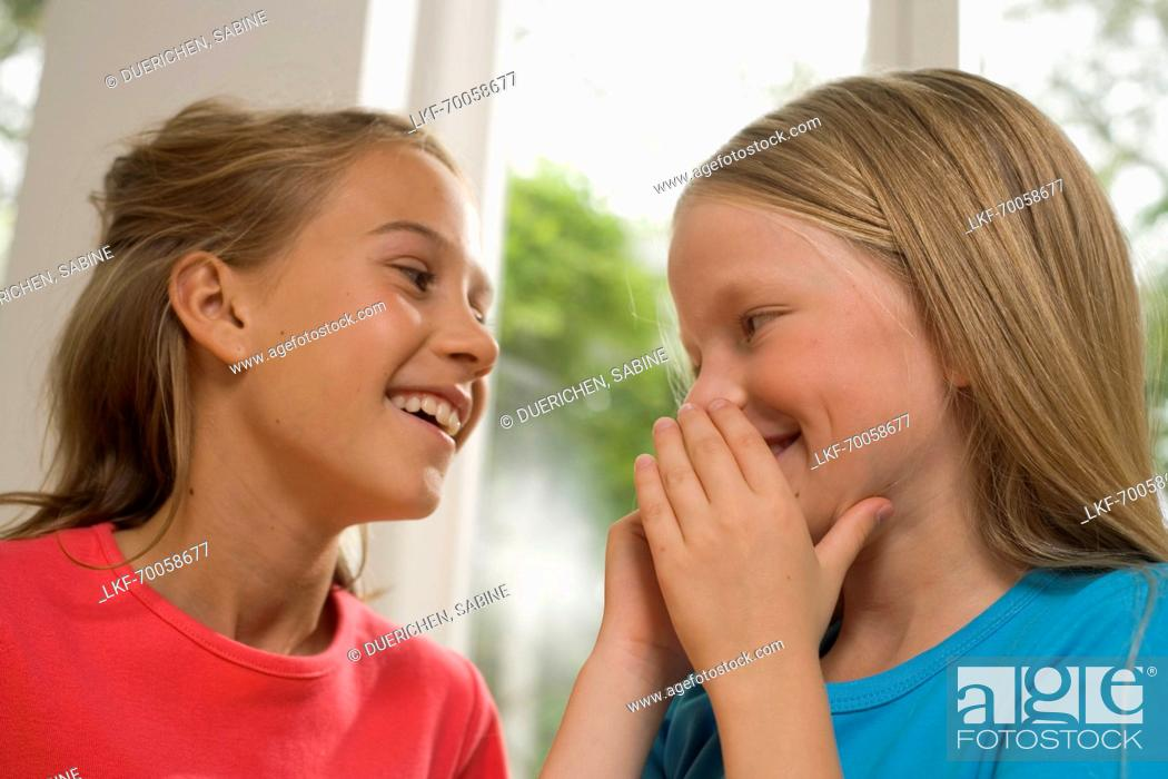 Stock Photo: Girl whispering into girlfriend's ear, children's birthday party.